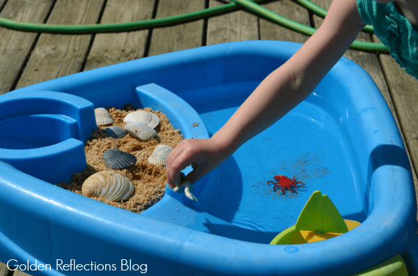 Playing with beach themed water sensory table for toddlers.
